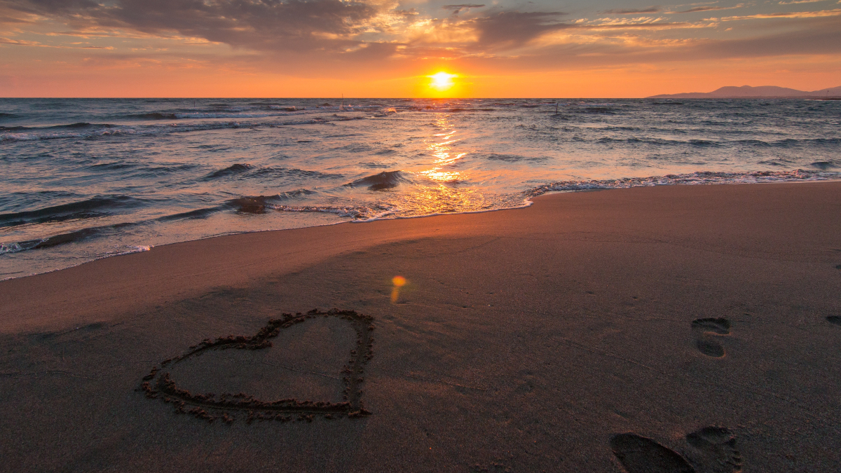 heart in sand at beach sunset