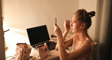 woman at desk with laptop doing her makeup